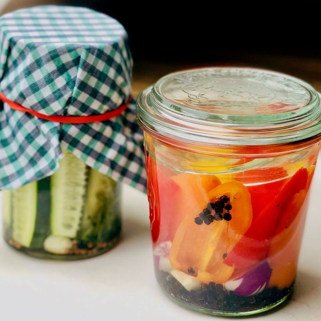 Zwei Gläser mit fermentiertem Gemüse: Paprika und Gurken